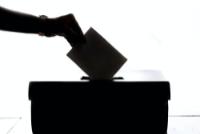 Une main glisse une enveloppe dans une urne.