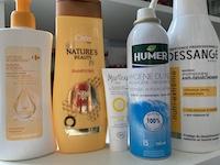 Cinq bouteilles de produit cosmétiques. Ils sont décrits dans le billet.