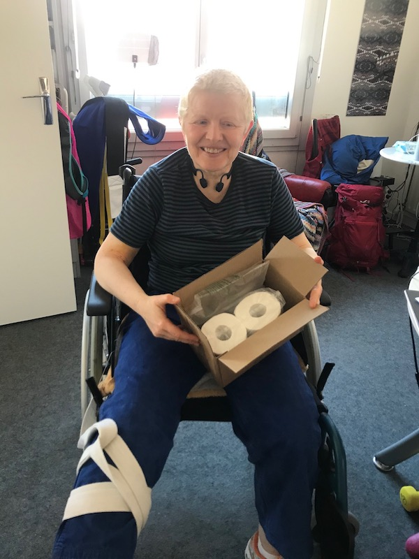 Je suis dans un fauteuil roulant, un carton avec deux rouleaux de pQ sur les genoux.