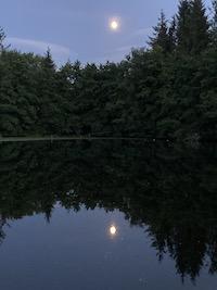 La lune se reflète dans l'eau d'un lac