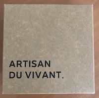 """La photo montre la boite d'emballage en carton avec le slogan """"Artisan du vivant""""."""
