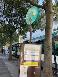 Un arrêt provisoire du 58. Un poteaux planté dans un socler avec les informations sur la circulation de bus. En fond, la ville.